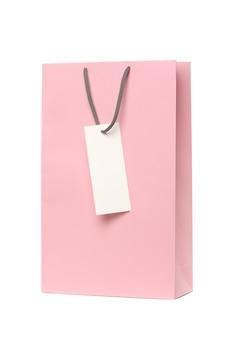 Sacchetto di imballaggio rosa con manici ed etichetta bianca isolata su sfondo bianco.