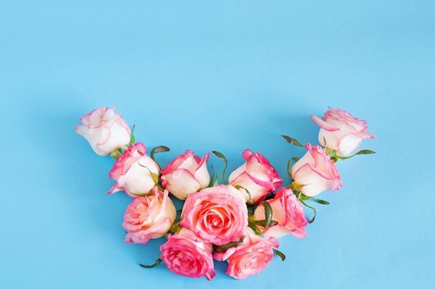 Spazio floreale rosa pallido con mazzo di rose sull'azzurro