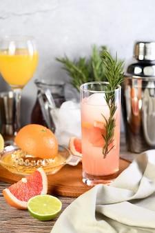 Cocktail paloma rosa con succo di pompelmo, tequila e rosmarino