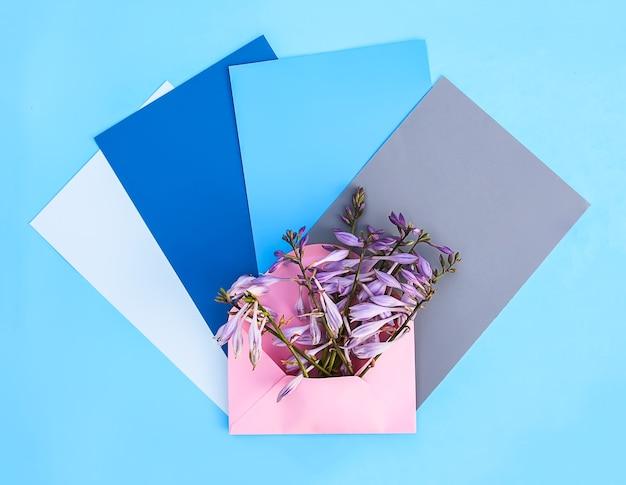 Busta di carta rosa con fiori freschi e luminosi da giardino e fogli di carta vuoti su sfondo azzurro. modello floreale festivo. progettazione di biglietti di auguri. vista dall'alto.