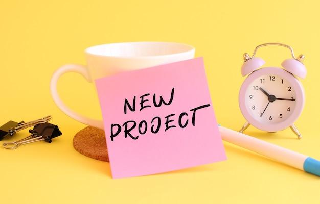 Carta rosa con il testo nuovo progetto su una tazza bianca. orologio su sfondo giallo.