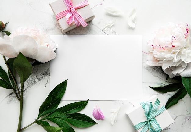 Peonie rosa con carta vuota e confezione regalo su sfondo bianco