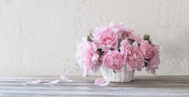 Peonia rosa in cesto su sfondo vecchio muro