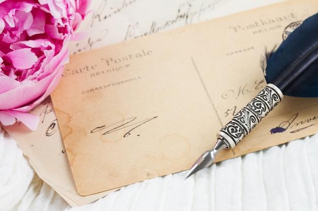 Fiore di peonia rosa con antica lettera in bianco con spazio di copia e penna piuma su pizzo bianco