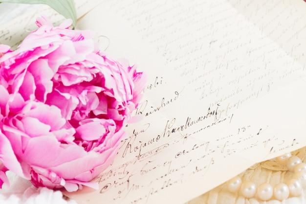Fiore di peonia rosa con antica lettera scritta a mano