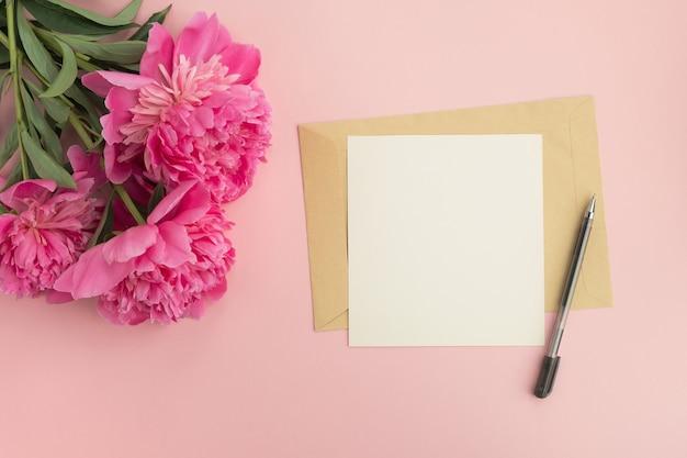 Fiori di peonia rosa e busta con scheda in bianco sul tavolo
