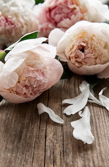 Fiori di peonia rosa su un vecchio tavolo di legno