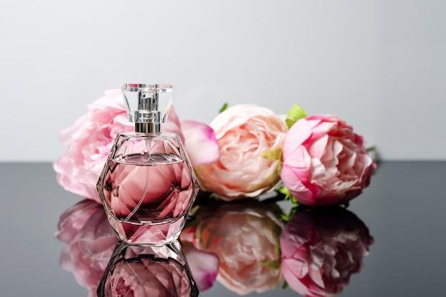 Bottiglia di profumo rosa con fiori sulla superficie in bianco e nero