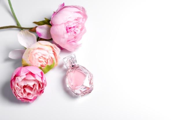 Bottiglia di profumo rosa con fiori sulla superficie chiara. profumeria, cosmetica, collezione di fragranze