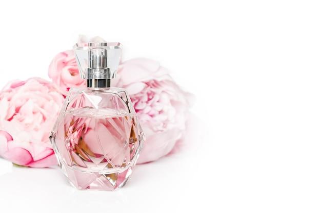 Bottiglia di profumo rosa con fiori sulla superficie chiara