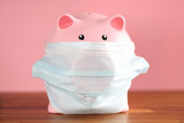 Salvadanaio di maiale rosa in maschera medica protettiva