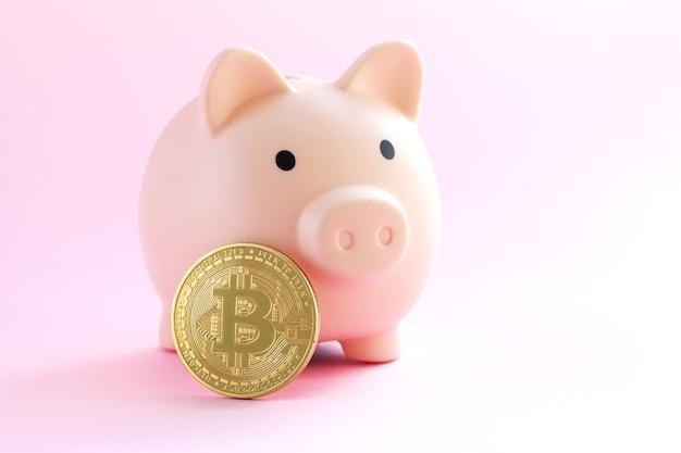 Salvadanaio rosa accanto al primo piano della moneta bitcoin