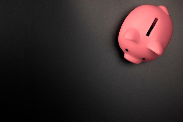 Salvadanaio rosa su sfondo nero vista dall'alto con copia risparmio di spazioconcetto finanziario e aziendale