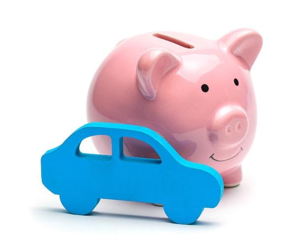Salvadanaio rosa e auto blu isolati su sfondo bianco concetto di risparmio di denaro sull'acquisto di un'auto