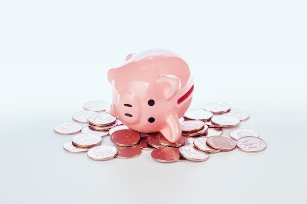 Porcellino salvadanaio rosa e monete isolati su bianco