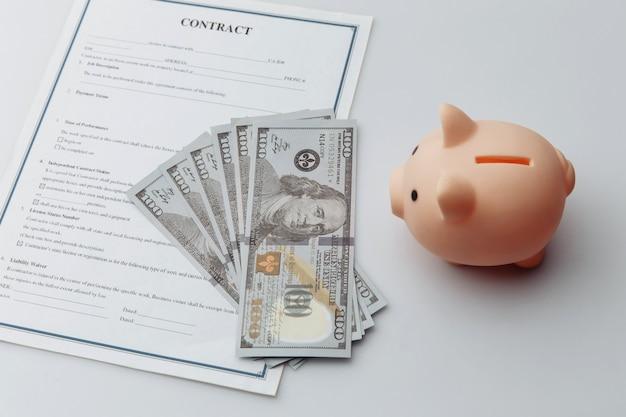 Porcellino salvadanaio rosa, contratto e soldi. economia e gestione del concetto finanziario.