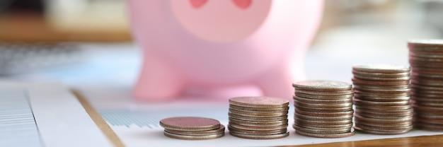Salvadanaio rosa con gli occhiali in piedi davanti a pile di monete closeup