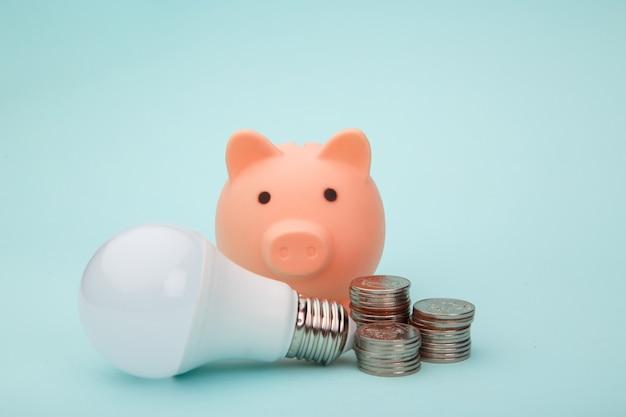 Salvadanaio rosa, lampada e monete sul blu, concetto di risparmio energetico.