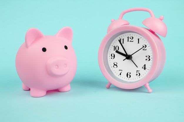 Salvadanaio rosa salvadanaio e orologio su sfondo blu. risparmio di denaro per investimenti futuri e concetto di pensionamento.