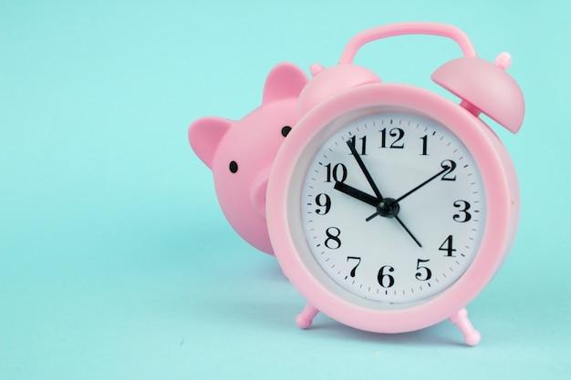 Salvadanaio rosa salvadanaio guardando intorno all'orologio su sfondo blu. risparmio di denaro per investimenti futuri e concetto di pensionamento.
