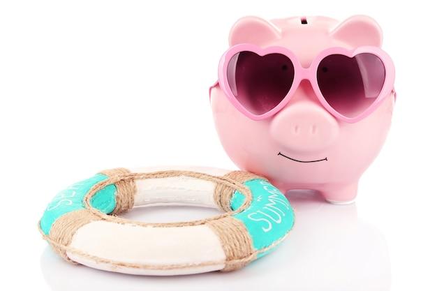 Salvadanaio rosa in occhiali da sole con salvagente su bianco