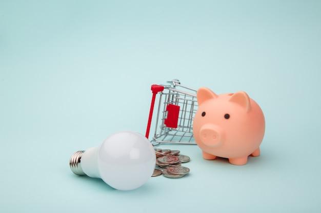 Salvadanaio rosa, carrello, lampada e monete, concetto di risparmio energetico