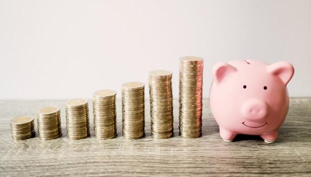 Salvadanaio rosa con grafico di crescita del mucchio di monete, risparmio di denaro per il futuro piano di investimento e concetto di fondo pensione.
