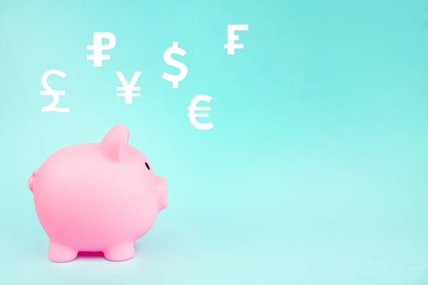 Salvadanaio rosa con valute mondiali ologramma digitale su sfondo blu. risparmio finanziario ed economia bancaria.