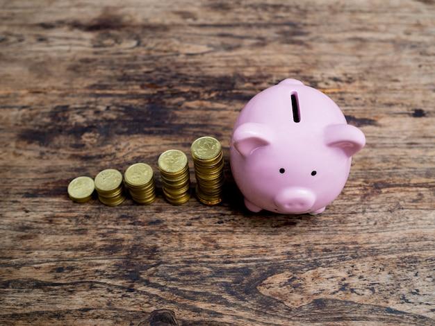 Salvadanaio rosa con grafico di crescita del mucchio di monete d'oro, risparmio di denaro per il futuro piano di investimento e concetto di fondo pensione.