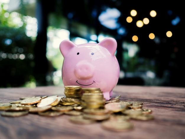 Salvadanaio rosa con mucchio di monete d'oro, risparmio di denaro per il futuro piano di investimento e concetto di fondo pensione.