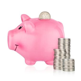 Salvadanaio rosa con pile di monete isolate su superficie bianca