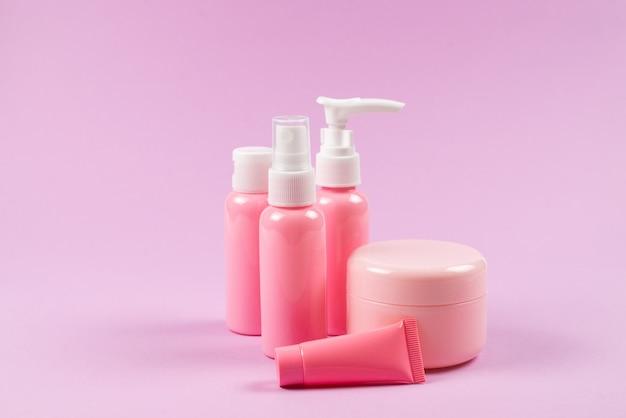 Bottiglie di plastica rosa per prodotti per l'igiene, cosmetici, prodotti per l'igiene su uno sfondo rosa.