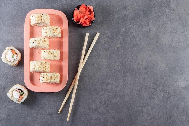 Piatto rosa di deliziosi rotoli di sushi con semi di sesamo su sfondo di pietra.