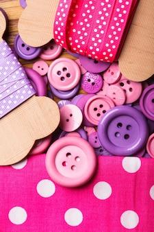Nastro rosa a pois, tessuto e bottoni per cucire