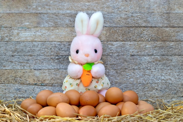 Bambola di coniglio rosa che tiene la carota con le uova sullo sfondo del tavolo in legno