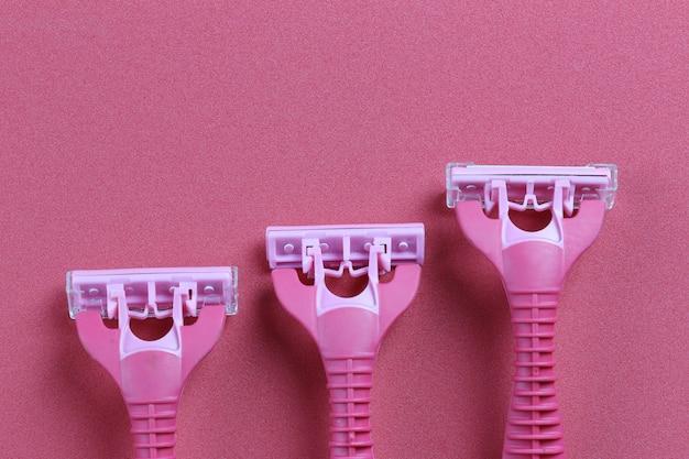 Rasoio rosa su sfondo rosso di carta patinata.