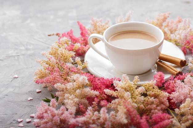 Fiori rosa e rossi di astilbe e una tazza di caffè