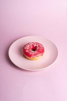 Ciambella rosa rossa con granelli bianchi sul piatto rosa, cibo dolce da dessert glassato sul minimo rosa, vista angolare