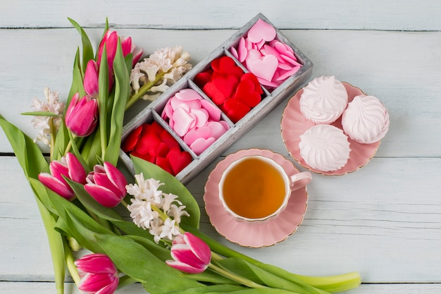 Cuori rosa e rossi in una scatola di legno, una tazza di tè e marshmallows e un bouquet di giacinti e tulipani