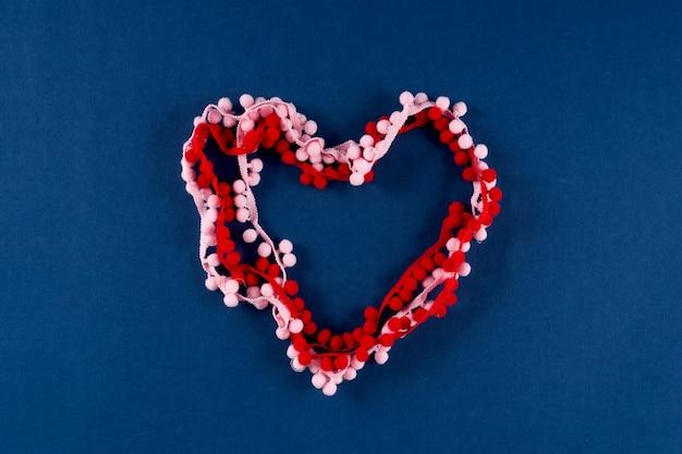 Nastri con pompon rosa e rossi su sfondo di colore blu classico 2020 di tendenza. concetto di san valentino 14 febbraio.