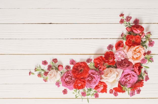 Rose rosa e rosse su fondo di legno bianco