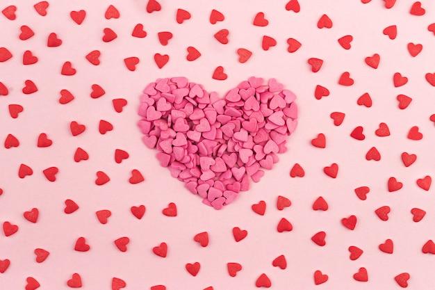 Rosa e rosso il giorno di san valentino a forma di cuore caramelle su uno sfondo color pastello. piatto laico, vista dall'alto cuori texture. concetto di amore santo valentino, biglietti di auguri per la festa della mamma, invito.