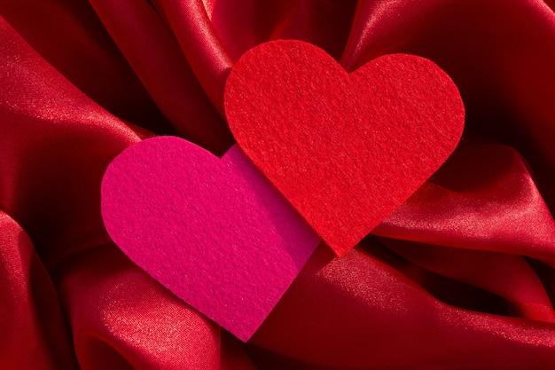 Cuori di velluto rosa e rosso su sfondo di tessuto di seta, vista dall'alto. concetto di san valentino
