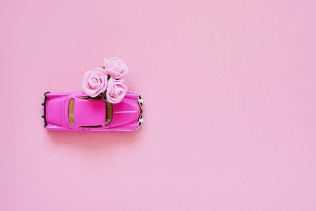 Auto giocattolo retrò rosa offrendo bouquet di fiori rosa sul rosa