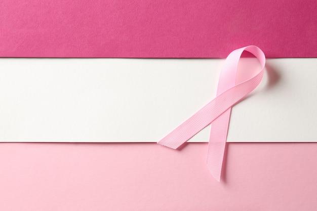Nastro rosa su sfondo colorato. concetto di consapevolezza del cancro al seno