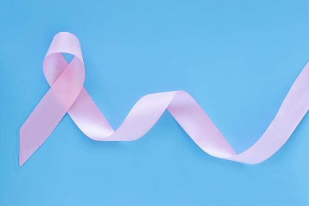 Arricciatura del nastro rosa su sfondo blu isolato con lo spazio della copia. cancro al seno e concetto di assicurazione.