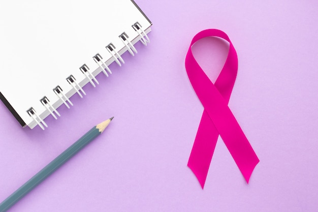 Nastro rosa e blocco note su un tavolo viola, il concetto di salute femminile, la lotta contro il cancro al seno