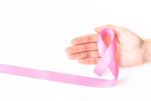 Simbolo rosa del nastro per il concetto di consapevolezza del cancro al seno in mano della donna