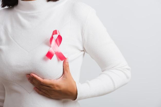 Nastro rosa sul petto della donna per la consapevolezza del cancro al seno
