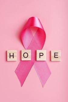 Nastro rosa e lettere in legno con la parola speranza su sfondo rosa, verticale